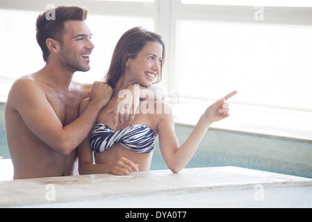 Couple de patauger dans une piscine intérieure à la fenêtre à afficher par Banque D'Images