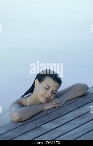 Woman in pool leaning against deck, reposant la tête sur les bras, les yeux fermés Banque D'Images