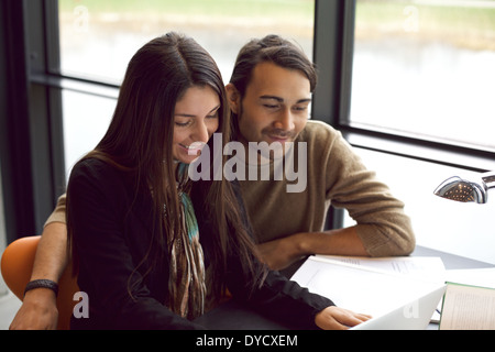 Deux jeunes étudiants assis ensemble à table à l'aide d'ordinateur portable. Camarades de classe avec des livres Banque D'Images
