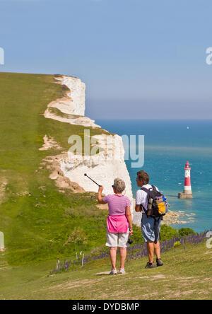 Les promeneurs sur les South Downs Way à Beachy Head avec Beachy Head Lighthouse en mer. Banque D'Images