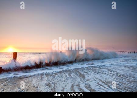 Happisburgh beach et la défense de la mer à l'abandon au lever du soleil sur la côte de Norfolk. Banque D'Images