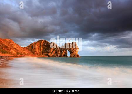 Une tempête coucher du soleil à Durdle Door dans le Dorset. Banque D'Images