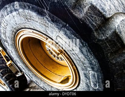 Gros plan des pneus et roues géantes sur un bulldozer montrant la saleté et l'usure sur les marches Banque D'Images