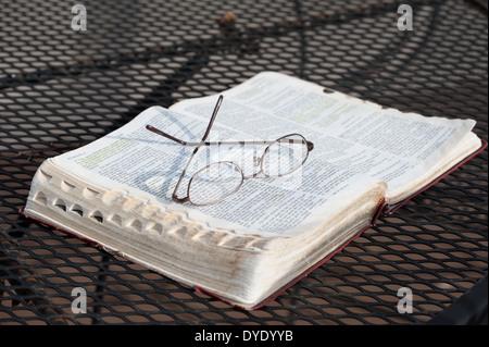 Un gros plan d'une paire de lunettes de lecture reposant sur une portée, Bible ouverte sur une table de patio en fer forgé