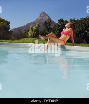 Belle jeune femme assise en piscine et profiter d'un bain de soleil. Portrait modèle féminin en bikini au soleil Banque D'Images