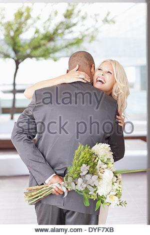 Femme avec des fleurs hugging man Banque D'Images
