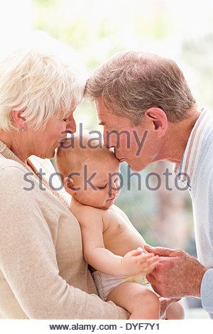 Les grands-parents holding et embrassant bébé Banque D'Images