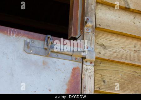 Coulissante en métal sur métal un porte en bois stable avec surround est prévue. Banque D'Images