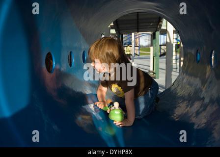 Trois ans à jouer dans une aire de tunnel au parc au bord de l'aéroport de Louisville, Kentucky Banque D'Images