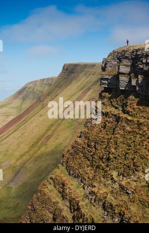 Female hiker sur Carmarthen Fans - Bannau avec Picws Du Sir Gaer en distance, Black Mountain, parc national de Brecon Banque D'Images