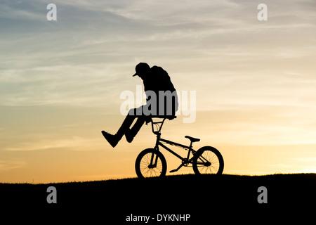 Jeune homme faisant des tours sur son vélo BMX. Silhouette Banque D'Images