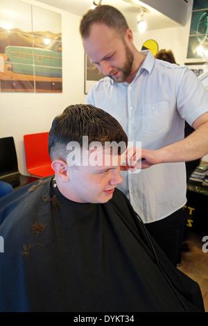 Teenage boy avoir couper les cheveux dans une boutique de barbier Banque D'Images