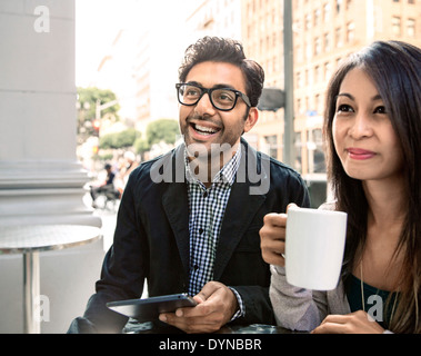 Couple enjoying coffee at sidewalk cafe Banque D'Images
