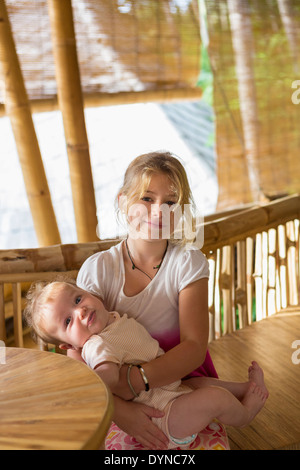 Caucasian girl holding baby sœur Banque D'Images