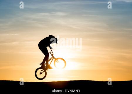 Jeune homme sur son vélo BMX sautant en l'air. Silhouette Banque D'Images