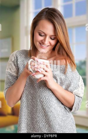 Woman smelling une tasse de café, prêt à boire, dans une chambre Banque D'Images
