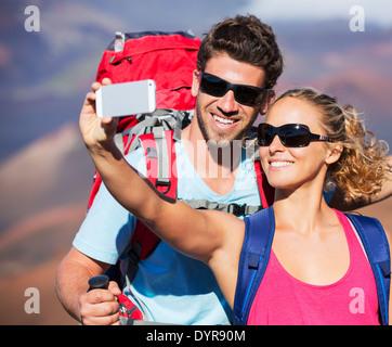 """Heureux couple taking photo d'eux-mêmes avec smart phone outdoors, prendre un """"70623"""" Banque D'Images"""