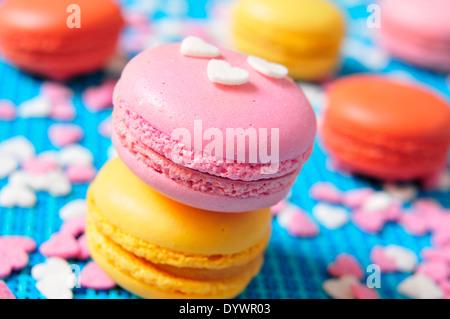 Certains macarons appétissants avec différentes couleurs et saveurs sur un fond bleu Banque D'Images
