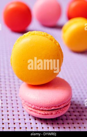 Certains macarons appétissants avec différentes couleurs et saveurs sur fond violet Banque D'Images