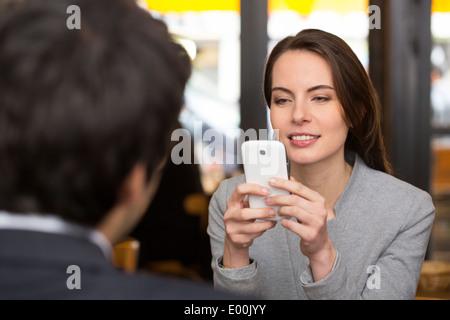 Femme Homme joyeux dîner smartphone sms web surf bar Banque D'Images