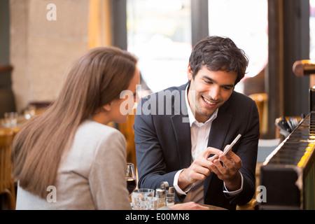 Man woman using cell phone bar café Banque D'Images
