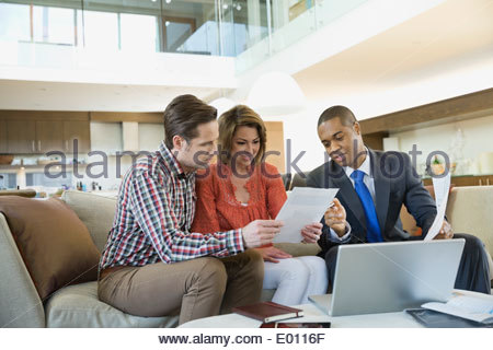 Couple de parler à un conseiller financier dans la salle de séjour Banque D'Images