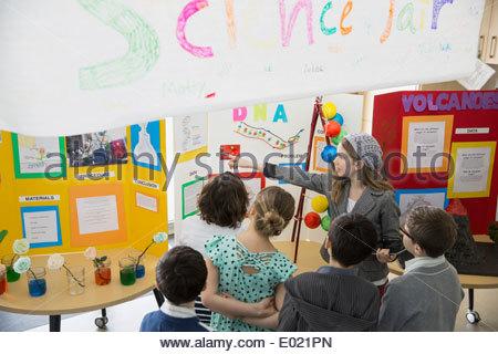 Fille de l'école d'expliquer à leurs camarades du projet d'expo-sciences Banque D'Images