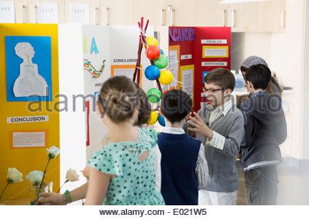 School boy expliquant à leurs camarades du projet d'expo-sciences Banque D'Images