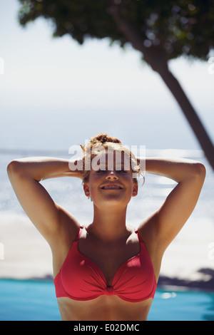 Young woman relaxing in swimming pool et souriant sur une chaude journée d'été. Caucasian female model wearing bikini Banque D'Images