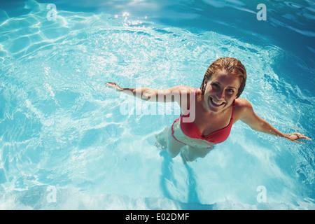 Jeune fille heureuse de vous détendre dans une piscine. Smiling young woman standing in maillots de piscine. Banque D'Images