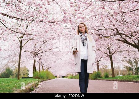 Belle jeune femme avec un téléphone mobile à écouter de la musique dans le parc en fleurs au printemps. Attractive young woman enjoying music. Banque D'Images