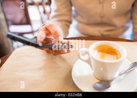 Smart phone femelle sms mail bar café Banque D'Images