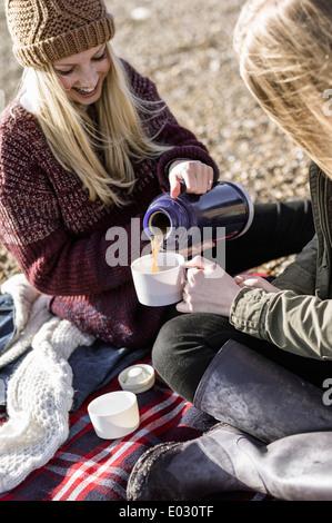 Deux jeunes filles ayant un pique-nique d'hiver sur la plage.