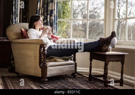 Une jeune femme de détente à la maison avec ses pieds vers le haut d'avoir une tasse de thé.