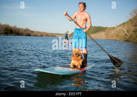 Un homme debout sur un paddleboard avec un chien. Banque D'Images