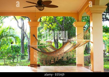 Un hamac est suspendu sur un porche ensoleillé avec les tropiques dans l'arrière-plan.