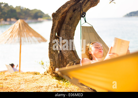 Lady reading book in hammock. Banque D'Images