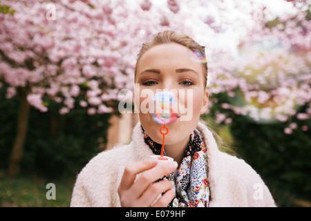 Portrait de belle jeune femme faisant des bulles au parc. Joli modèle féminin avec bulle baguette sur le jardin Banque D'Images