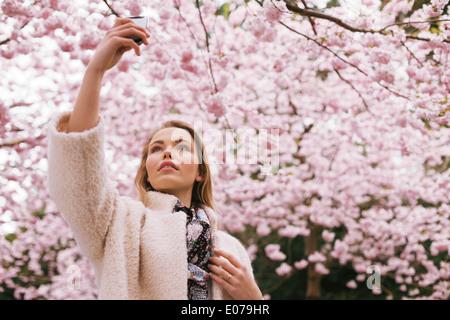 Belle jeune fille photographier la nature avec son téléphone mobile. Jolie jeune femme à fleur de printemps park Banque D'Images