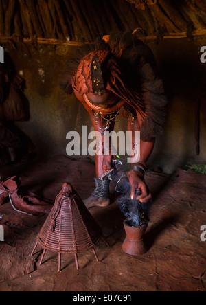 Femme Himba en utilisant de l'encens pour purifier elle-même et ses vêtements, Epupa, Namibie Banque D'Images