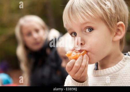 Portrait of boy eating orange dehors Banque D'Images