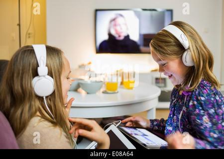 Heureux soeurs listening music sur tablettes numériques dans la salle de séjour Banque D'Images