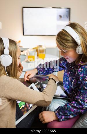L'écoute des sœurs de la musique sur tablettes numériques dans la salle de séjour Banque D'Images