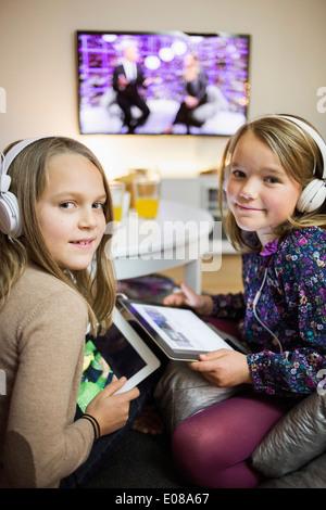 Portrait of smiling sisters listening music sur tablettes numériques dans la salle de séjour Banque D'Images