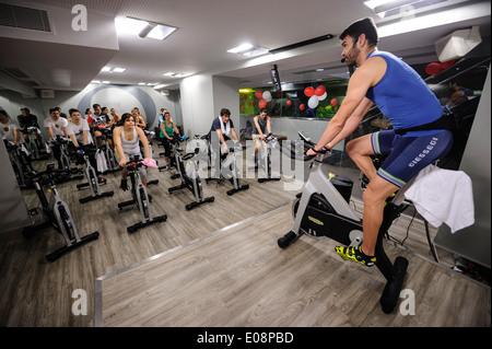 Instructeur de conditionnement physique en face de personnes équitation des bicyclettes stationnaires pendant un Banque D'Images