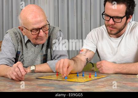 Grand-père et petit-fils jouer ensemble ludo à la maison Banque D'Images