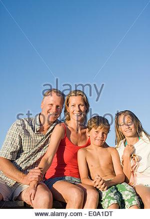 Family sitting on pier ensemble Banque D'Images