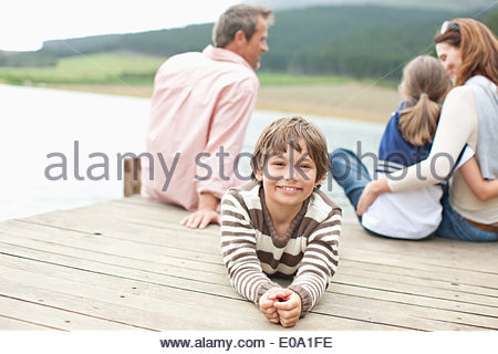 Family sitting on pier by lake Banque D'Images