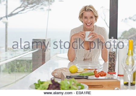 Woman drinking coffee in kitchen Banque D'Images