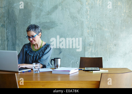 Femme mature at conference table working on laptop Banque D'Images